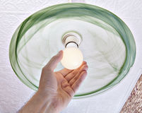 Hand twists energy-saving LED lamp on ceiling light. Stock Photo