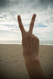 Hand with two fingers up in the peace or victory Stock Photos