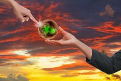 Hand two point on world hot on sky red idea global warming on sky red sunset background.  Royalty Free Stock Image