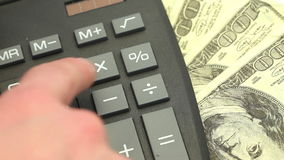 Hand typing on a calculator surrounded by bills stock footage
