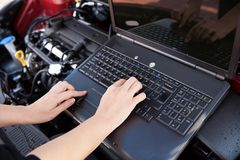 Hand typing on a computer in a garage Royalty Free Stock Images