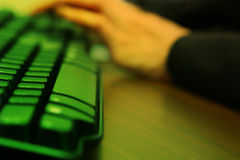 Hand typing on keyboard. Hand typing on computer keyboard with focus on buttons Stock Photos