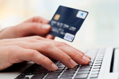 Hand typing on laptop with credit card. Stock Image