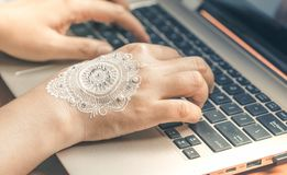 Hand Typing Laptop Keyboard. Woman Hand with Mandala Henna Art. Hand typing on laptop keyboard. Woman hand with mandala design henna art. Concept of working from royalty free stock photos