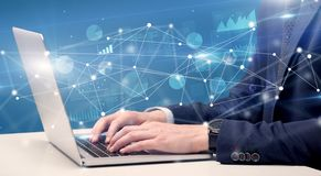 Hand typing on laptop with linked report and charts around. Businessman typing on laptop with linked reports charts grapghs around royalty free stock images