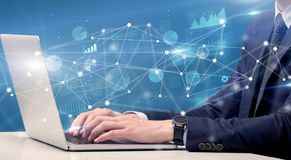 Hand typing on laptop with linked report and charts around. Businessman typing on laptop with linked reports charts grapghs around stock photo