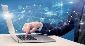 Hand typing on laptop with linked report and charts around. Businessman typing on laptop with linked reports charts grapghs aroundn stock photography