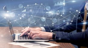 Hand typing on laptop with linked report and charts around. Businessman typing on laptop with linked reports charts grapghs aroundn royalty free stock images