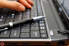 Hand typing on laptop with pen Stock Images