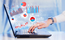 Hand typing on modern laptop notebook computer with graph icons Royalty Free Stock Images