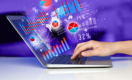 Hand typing on modern laptop notebook computer with graph icons Stock Photo