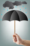 Hand with umbrella. Male hand holding a black umbrella while sheltering from the rain Royalty Free Stock Photo