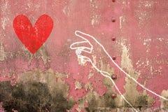 Hand und Arm, die für rotes Herz, Hand gezeichnet auf Backsteinmauer erreicht Lizenzfreies Stockbild
