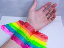 Hand und ein Regenbogen im Kampf stockfotos
