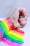 Hand und ein Regenbogen im Kampf stockbilder