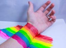 Hand und ein Regenbogen im Kampf Stockfoto