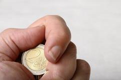Hand und Finger, die eine Münze des Euro zwei anhalten Stockfoto