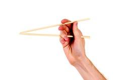 Hand und hölzerne Ess-Stäbchen der Frau Stockfoto