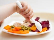 Hand und Platte des Schätzchens mit Gemüse Lizenzfreie Stockbilder