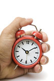 Hand und rote Alarmuhr Stockfotografie