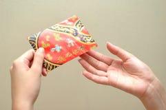 Hand und rotes Paket Stockfoto