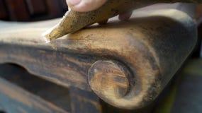Hand und Sandpapier versanden das Abwischen eines Sofaarmes Stockfoto