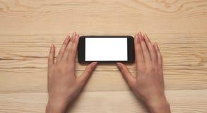 Hand und Telefon auf hölzernem Hintergrund lizenzfreies stockfoto