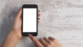 Hand und Telefon auf hölzernem Hintergrund stockfotos