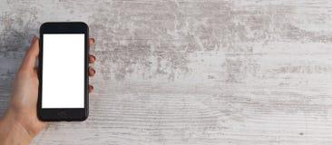 Hand und Telefon auf hölzernem Hintergrund stockbilder