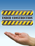 Hand under construction sign blue Stock Images