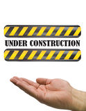 Hand under construction sign white Stock Photos