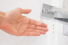 Hand under running water at bathroom sink Royalty Free Stock Image