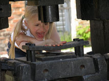 Hand under the stamping press. Girl in the park of historical engines Stock Image