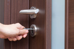 Hand unlocking house door. Hand unlocking house front door Royalty Free Stock Photography