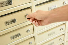 Hand unlocking mailbox with a key. Hand unlocking wooden mailbox with a key Royalty Free Stock Image