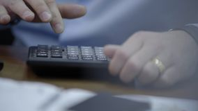 Hand of unrecognizable businessman using calculator - closeup shot. HD stock footage