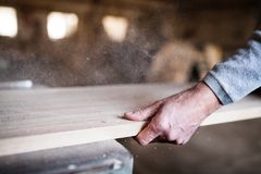 An unrecognizable man worker in the carpentry workshop, working with wood. Royalty Free Stock Photo