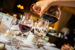 Hand pouring red wine to glass stock images