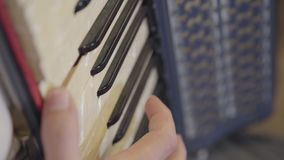 The hand of an unrecognized man playing the keys of the button accordion close-up. The hand of an unrecognized man playing the keys of the button accordion stock video
