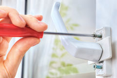 Hand unscrews the bolt, using a screwdriver, dismantling window Stock Photos