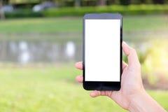 Hand unter Verwendung des Handys im Park stockbild