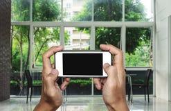 Hand unter Verwendung des Handys, leerer Kopienraum auf Schirm, Innenlebensraumhintergrund Stockfotografie