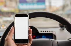Hand unter Verwendung des intelligenten Telefons am Lenkradauto stockfotos