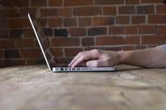 Hand unter Verwendung des Laptops Lizenzfreie Stockbilder