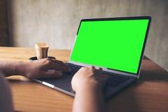 Hand unter Verwendung des Laptops mit leerem Tischplattenschirm mit Kaffeetasse auf Holztisch Lizenzfreies Stockfoto