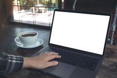 Hand unter Verwendung des Laptops mit leerem weißem Tischplattenschirm mit Kaffeetasse auf Holztisch im Café Stockbild