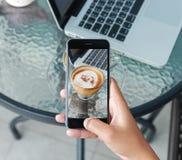 Hand unter Verwendung des Telefons, das Foto auf Kaffeegetränk macht Lizenzfreie Stockbilder