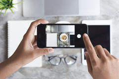 Hand unter Verwendung des Telefons machen Foto auf Arbeitsschreibtisch Stockfotos