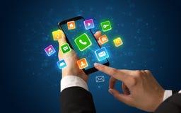 Hand unter Verwendung des Telefons mit glänzenden Anwendungsikonen Lizenzfreies Stockfoto