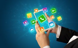Hand unter Verwendung des Telefons mit glänzenden Anwendungsikonen Stockfoto